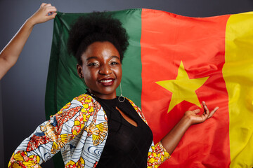 African woman in national clothes posing and dancing against flag of Cameroon