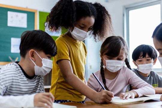 A group of Kids students wearing medical masks in the classroom.