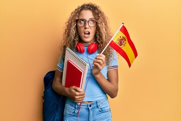 Beautiful caucasian teenager girl exchange student holding spanish flag angry and mad screaming frustrated and furious, shouting with anger. rage and aggressive concept.