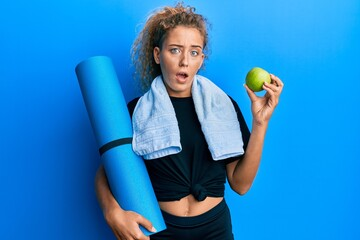 Beautiful caucasian teenager girl holding yoga mat and green apple in shock face, looking skeptical and sarcastic, surprised with open mouth