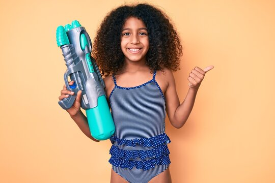African american child with curly hair wearing swimwear and holding water gun pointing thumb up to the side smiling happy with open mouth