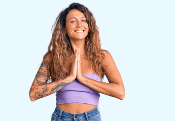 Young hispanic woman with tattoo wearing casual clothes praying with hands together asking for forgiveness smiling confident.