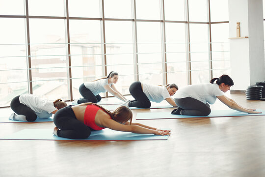 Pregnant women in a gym. Girls diong yoga. Women working with a coach.