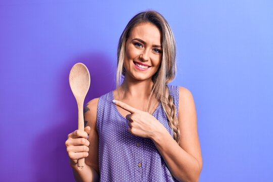 Young beautiful blonde woman holding wooden spoon over isolated purple background smiling happy pointing with hand and finger