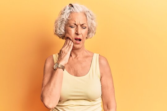 Senior grey-haired woman wearing casual clothes touching mouth with hand with painful expression because of toothache or dental illness on teeth. dentist