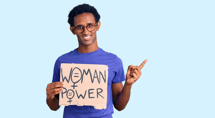 African handsome man holding woman power banner smiling happy pointing with hand and finger to the...