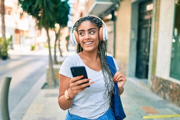 Young african american student woman smiling happy using smartphone at the university campus