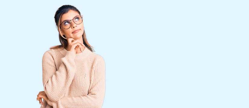 Young beautiful woman wearing casual winter sweater and glasses serious face thinking about question with hand on chin, thoughtful about confusing idea