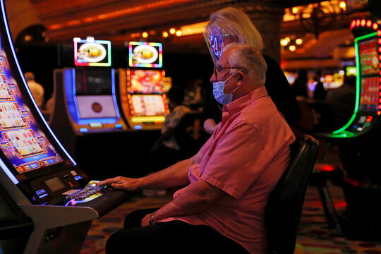 People wearing protective face masks play slot machines amid the coronavirus disease (COVID-19) outbreak, at a casino outside the French Quarter in New Orleans, Louisiana