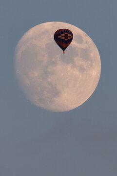 Hot air balloon floats past a rising moon in California