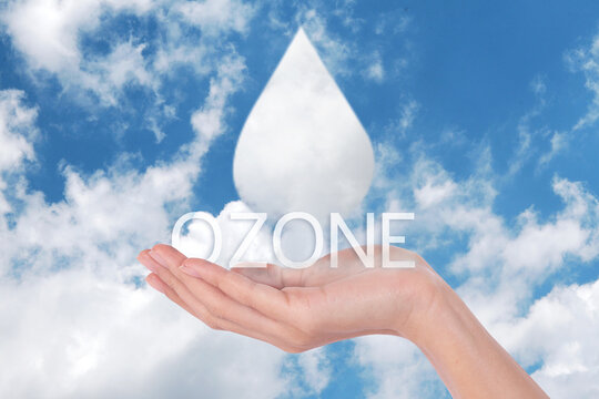 Clouds shaped like drops ozone of water in woman hands on blue sky background