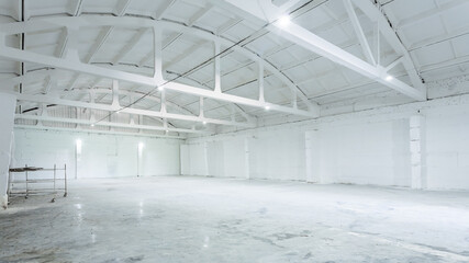 The interior of a huge industrial warehouse made of white bricks with a high ceiling for storing goods. The concept of storage of goods by importers, exporters, wholesalers, transport enterprises