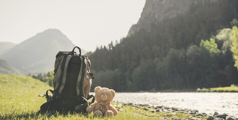 Backpack and teddy bear in the mountains