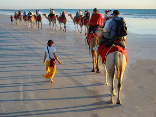 Tourist taking a camel ride on Cable Beach at sunset, Broome - Australia