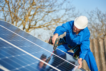 Man worker in blue suit and protective helmet installing solar photovoltaic panel system using screwdriver. Electrician mounting blue solar module on roof of modern house. Alternative energy concept.