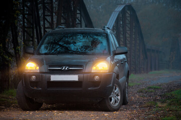 Perechin, Ukraine - OCT 20, 2019: suv headlights in foggy darkness. car on the old metal bridge with turned on light in mist environment