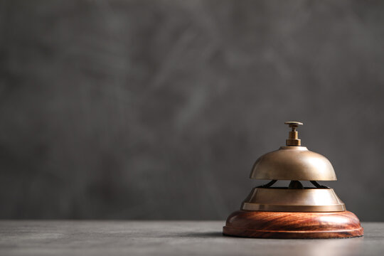 Hotel service bell on grey table. Space for text