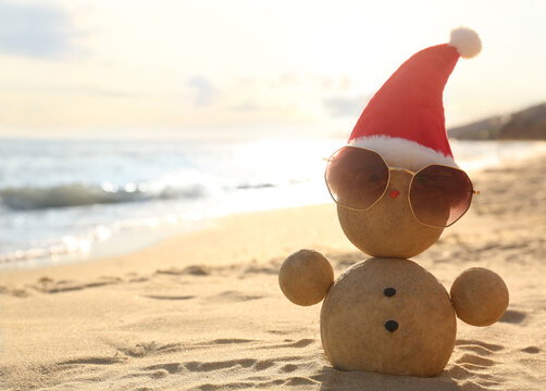 Snowman made of sand with Santa hat and sunglasses on beach near sea, space for text. Christmas vacation