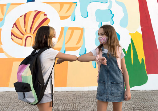 Two schoolchildren wearing protective masks greet each other with their elbows as they enter the school. Concept Back to school with Covid
