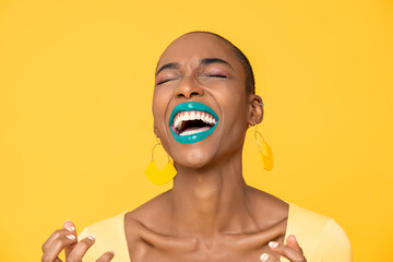 Close up portrait of laughing young African American woman with fashionable colorful make up isolated on yellow studio background