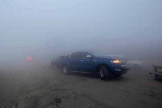 fagaras, romania - JUN 26, 2017: cars in the fog on the transfagarasan road 7C. low visibility, headlight do not help. dramatic weather