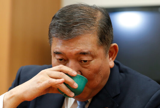 Japan's ruling Liberal Democratic Party lawmaker Shigeru Ishiba drinks a tea during an interview with Reuters at his office in Tokyo