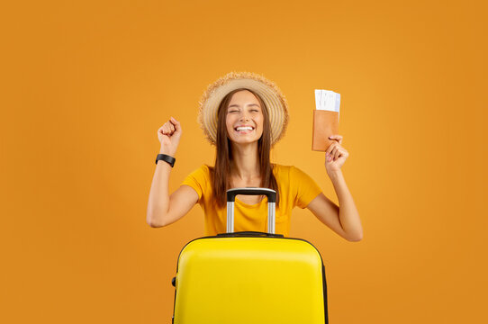 Excited girl with luggage holding passport and flight tickets