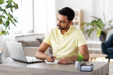remote job, technology and people concept - young indian man with notebook and laptop computer at home office
