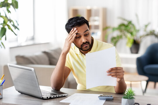 remote job, technology and people concept - stressed young indian man with calculator and papers working at home office
