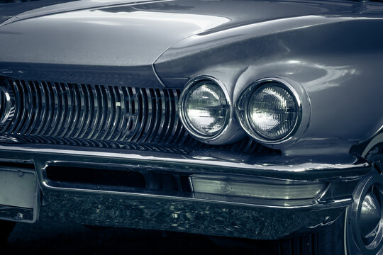 Partial view of a beautiful silver colored vintage car from the fifties