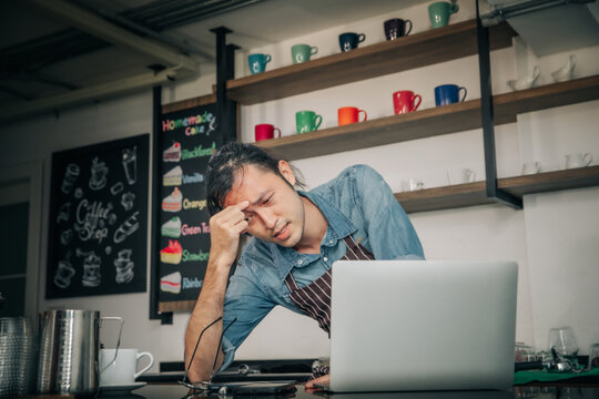 Coffee cafe  owner checking monthly reports on a tablet, bills and expenses of his small business. Start-up entrepreneur concerned about financial reports