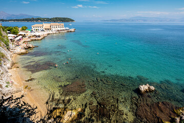 Stunning top view on the pebbly beach and turquoise water Corfu harbor with people swimming underneath from the esplanade lookout. Greece 2020