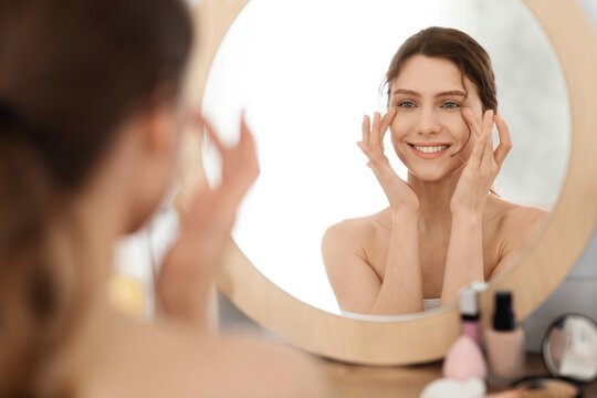 Young woman massaging eye zone, looking at mirror