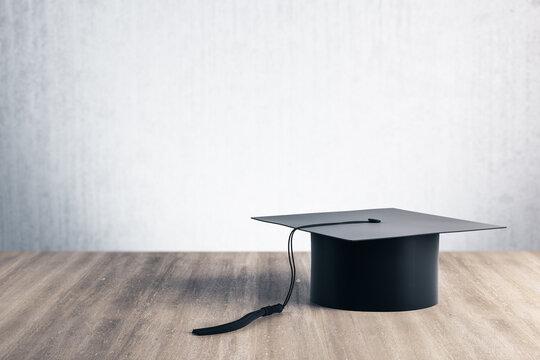 Black graduation cap on wooden table.