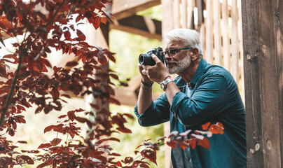 A mature man with a beard and a camera takes pictures, paparazzi. Retired active hobby, senior journalist.