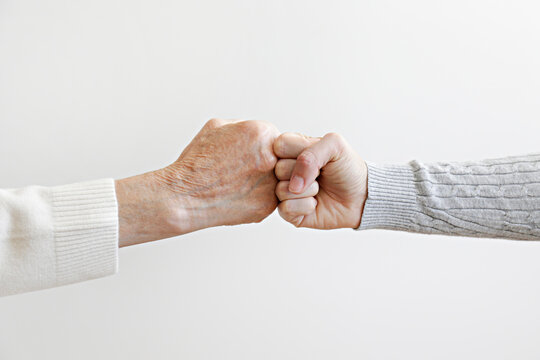 Two women of different age fist bumping over white wall background. Grandmother bonding with her granddaughter. Close up, copy space for text, isolated.