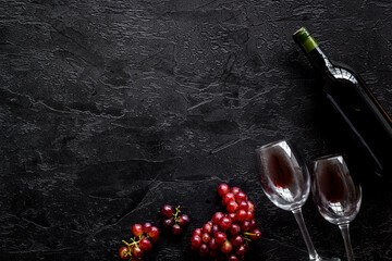 Fototapete - Red wine with grape - in glasses and bottle - on black desk top view copy space