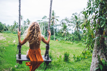 Anonymous curly haired woman sitting in swing and enjoying journey
