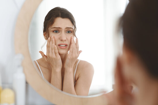 Stressed girl touching her skin and looking at mirror