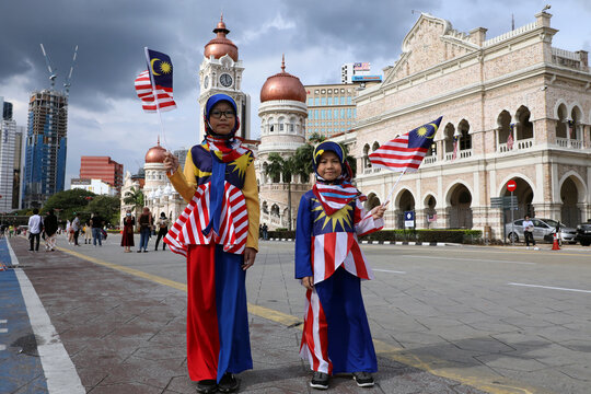Girls wearing costumes made of Malaysian flags pose for a picture at Independence Square during Malaysia Independence Day, in Kuala Lumpur