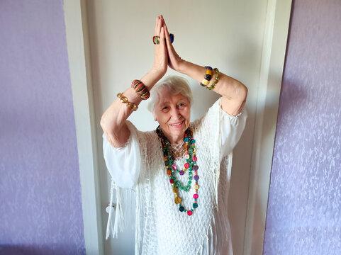 Happy smiling funny senior woman wearing beads dancing