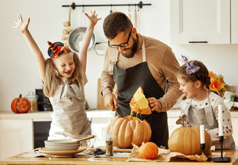 happy family   father and children prepare for Halloween by carving pumpkins at home in kitchen.
