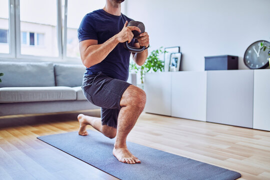 Home workout, closeup of athletic man doing lunges with kettlebell at home