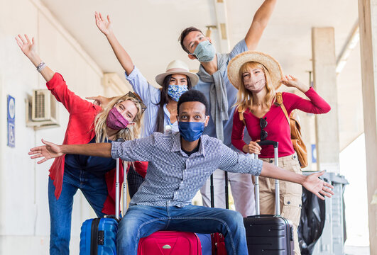 Multiracial group of friends at train station with luggage wearing protective mask. Tourism and holidays concept during Covid19 pandemic lockdown.