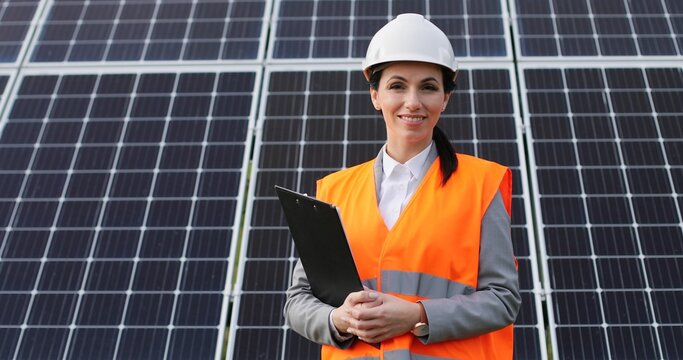 Portrait of female engineer on background field of photovoltaic solar panels. Woman technician at solar station.