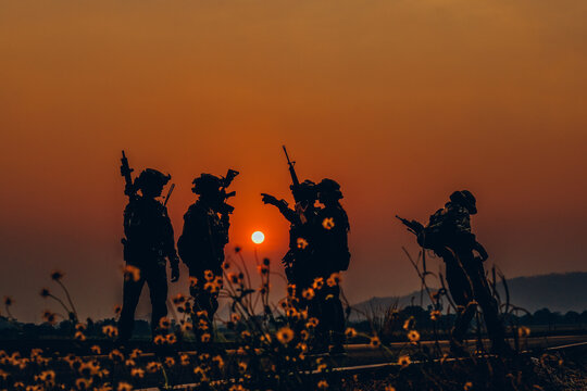 Silhouette Soldiers Against Orange Sky During Sunset