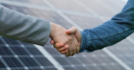 Close up view of shaking hands after discussion on background of photovoltaic solar panels.