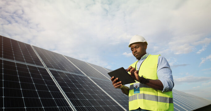 Portrait of african american electrician engineer in safety helmet and uniform using tablet checking solar panels.