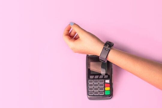 Payment for purchases using smart watches and POS terminal on light pink background. Contactless payment with NFC tecnology