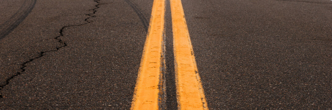 Asphalt background with two yellow road lines. Road markings on asphalt